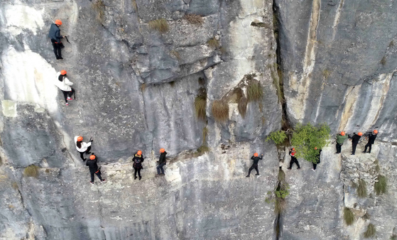 중국 후베이성 양쯔강 언스시의 산에 만들어진 '철길'에서 7일(현지시간) 산악동호인들이 암벽을 타고 있다. [신화=연합뉴스]