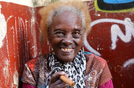 """올드 아바나 거리에서 촬영한 쿠바 할머니. 1쿡을 주고 사진을 찍었다. 이 할머니는 카메라를 든 외국인 관광객에게 """"뽀또? 원 쿡?""""하며 말을 걸었다. 카메라를 들이대자 자연스럽게 시가를 집었다. 손민호 기자"""