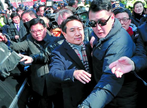 자유한국당 김진태 의원(가운데)이 12일 광주시·전남도당을 방문했다가 5·18 단체 회원들의 항의를 받자 경호원에 둘러싸여 이동하고 있다. 일부 시위자는 김 의원을 향해 쓰레기를 던지며 항의했다. [연합뉴스]