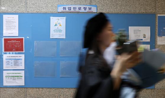 지난해 8월 서울의 한 대학교에서 후기 학위수여식을 마친 학부 졸업생이 텅 빈 취업 정보 게시판 앞을 지나고 있다. [뉴스1]