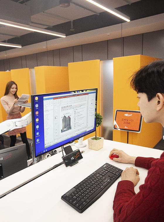 SK텔레콤 모델들이 5G VDI 도킹 시스템을 이용하고 있는 모습. 스마트폰을 케이블에 연결하기만 하면 모니터에 개인 작업창이 나타난다. [사진 SK텔레콤]