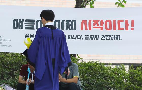 """지난해 8월 서울 모 대학에서 열린 후기 학위수여식에서 한 졸업생이 """"얘들아, 이제 시작이다!""""라고 적힌 플래카드 앞을 지나고 있다. [연합뉴스]"""