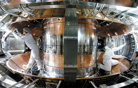 대전 국가핵융합연구소(NFRI) 연구원들이 2010년 KSTAR의 플라스마 실험을 앞두고 초전도 토카막 진공용기 내부를 보호하기 위해 열에 강한 탄소 계열의 특수 타일을 붙이고 있다. [사진 국가핵융합연구소]