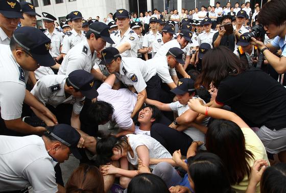 """경찰이 지난 2011년 8월 12일 오후 국회의사당 본청 앞에서 """"반값등록금 실현""""을 요구하며 항의 시위를 벌이는 대학생들을 연행하고 있다. [중앙포토]"""