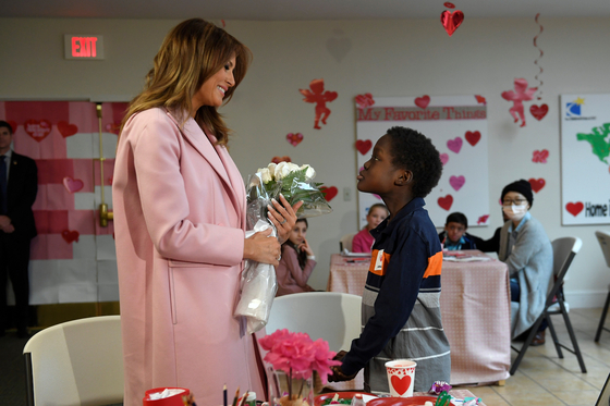 First lady Melania Trump is presented with a bouquet of flowers from Amani, 13, of Mombasa, Kenya, during her visit to the National Institutes of Health to see children at the Children's Inn in Bethesda, Md., Thursday, Feb. 14, 2019, and celebrate Valentine's Day. Amani also presented the first lady with a necklace that matched his bracelet. (AP Photo/Susan Walsh)
