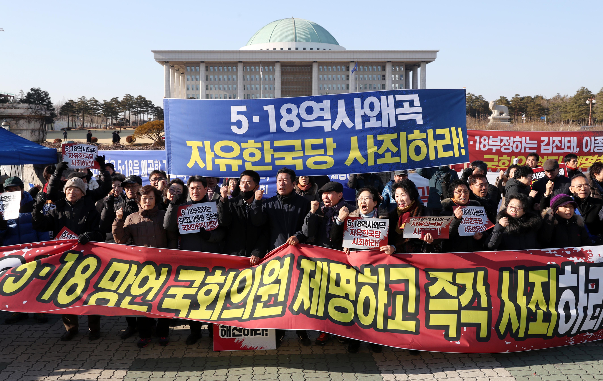 5·18 관련 단체 관계자들이 13일 오후 국회 정문 앞에서 자유한국당 일부 의원의 5·18 망언 관련 규탄 집회를 하고 있다. [연합뉴스]