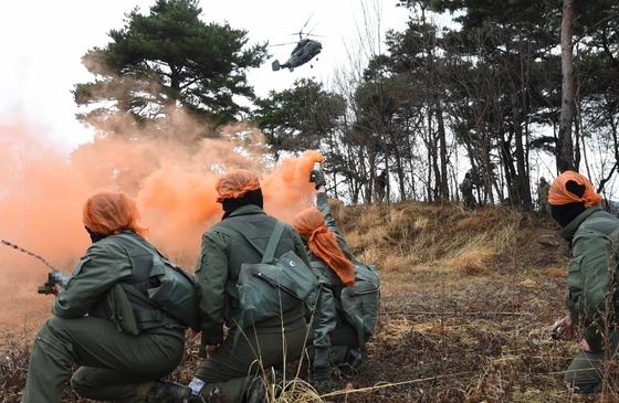 연막탄을 터뜨리고 무전기로 교신하면서 탐색구조헬기를 유도하는 모습 [사진 공군]