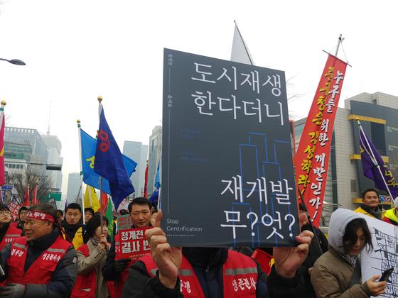 19일 열린 을지로 재개발 반대 집회. 참가자들이 피켓을 들고 중구청을 향해 행진하고 있다. 김정연 기자