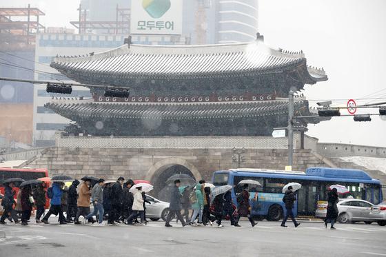 전국이 흐리고 중부지방에 대설주의보가 발효된 19일 오전 서울 중구 숭례문 인근에서 시민들이 발걸음을 재촉하고 있다. [뉴스1]