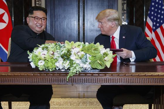 도널드 트럼프 미국 대통령과 김정은 북한 국무위원장이 12일 싱가포르 카펠라 호텔에서 합의문에 서명한 후 미소짓고 있다. [AP=연합뉴스]