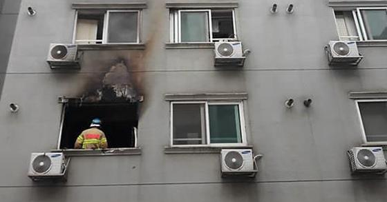 19일 낮 12시 17분쯤 불이 난 충남 천안의 한 오피스텔 모습.한 소방관이 화재 현장에서 잔불을 정리하고 있다. [연합뉴스]
