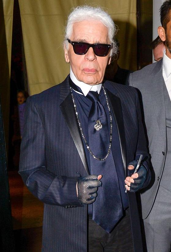 어두운 컬러의 슈트와 검정 선글라스, 뒤로 묶은 흰 머리, 그리고 손가락 장갑차림은 생전의 칼 라거펠트가 즐겼던 트레이드 마크였다.