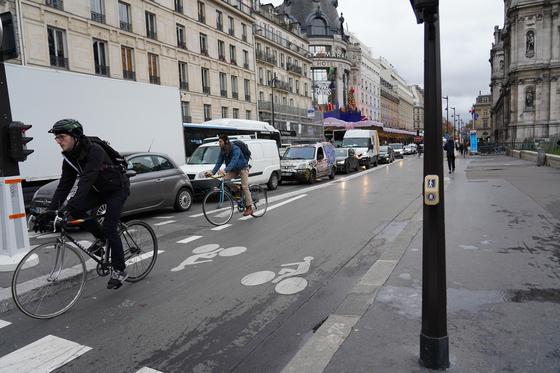 파리시처 앞 도로에서 자전거를 탄 시민들이 꽉 막힌 차량 행렬을 지나고 있다. 파리시는 친환경등급제 시행과 함께 도로를 줄이는 대신 자전거도로를 넓히는 등 대체 교통수단을 확대하고 있다. 천권필 기자.