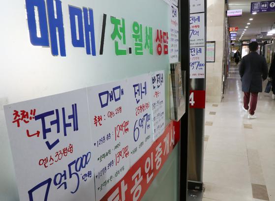 지난달 서울 아파트 임대차 계약 중 전세 비율이 73%를 넘기며 2013년 이후 가장 높았다. 전세 계약이 늘어도 전세 물량이 넉넉해 전셋값은 내림세다. 서울 부동산중개업소에 매매와 전세 매물 안내판이 붙어있다. [뉴스1]