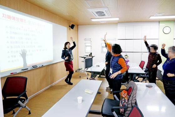 지난 24일 경기도 안산시 단원치매안심센터에서 치매 예방 수업이 진행 중이다. 강사를 따라 건강체조를 하는 노인들. 장진영 기자