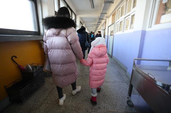 서울 공립초등학교 신입생 예비소집일인 지난달 8일 오후 서울 용산구 신용산초등학교에서 엄마손을 잡은 예비 신입생이 학교를 둘러보고 있다. [연합뉴스]