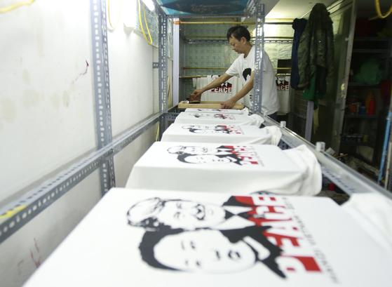 베트남 의류 사업자 트롱 탄 둑 씨가 21일(현지시간) 트럼프 미국 대통령과 김정은 북한 국무위원장의 얼굴이 새겨진 티셔츠를 제작하고 있다. [AP=연합뉴스]