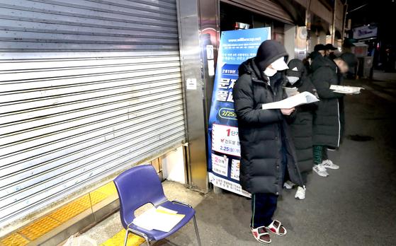 경찰 공무원 시험을 준비하는 수험생들이 지난 17일 오전 서울 노량진 윌비스학원에서 강의실 앞자리를 잡기 위해 순서를 기다리고 있다. 이 학원은 강의실 자리를 착주일에 한 번씩 선착순으로 결정한다. 600명이 들어가는 대형 강의실에서 칠판이 보이는 중앙 자리를 차지하기 위해서다. [최승식 기자]