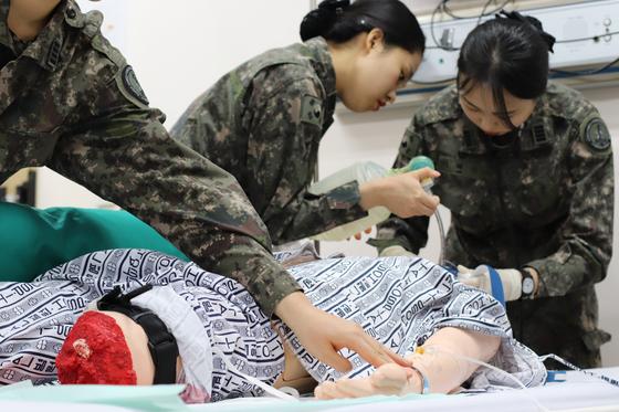 3월 소위 임관을 앞둔 국군간호사관학교 4학년 생도가 발목 지뢰를 밟아 다리가 절단 된 부상 환자 '휴먼 시뮬레이터' 응급 처치를 하고 있다. [박용한]