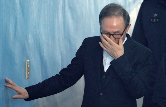 ?이명박 전 대통령이 1월 30일 호송차에서 내린 뒤 벽을 짚어가며 서울고등법원 법정을 향하고 있다. / 사진:연합뉴스