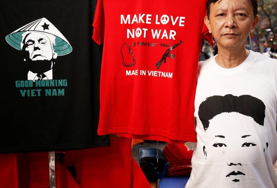 베트남 의류 사업자 트롱 탄 둑 씨가 21일(현지시간) 트럼프 미국 대통령과 김정은 북한 국무위원장의 얼굴이 새겨진 티셔츠를 소개하고 있다. [AP=연합뉴스]