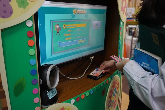 대만 타이베이 난강초등학교에서는 금융지식과 새기술을 적극적으로 도입해 교육한다. 사진은 한 학생이 자신의 학생증을 도서관 내 자동지급기(ATM)에 갖다 대 가상화폐 보유량을 확인하는 모습.[중앙포토]