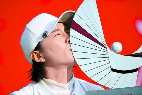 LPGA 투어에서 11년째를 맞는 양희영. 24일 혼다 타일랜드에서 대회 세 번째 우승을 차지한 뒤 트로피에 입을 맞추고 있다. 후원사를 구하지 못한 그는 이날 로고가 없는 민모자를 쓰고 경기했다. [AFP=연합뉴스]