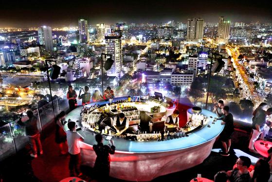 베트남은 1986년 개혁·개방 정책인 도이모이 정책을 채택한 뒤 외국자본이 물밀듯이 들어오며 빠르게 성장했다. 호찌민은 베트남의 경제 중심지답게 온 도시가 변화의 물결을 맞고 있다. 호찌민시에서 가장 유명한 루프톱 바인 칠스카이 바에서 관광객과 일부 부유한 베트남 젊은이들이 야경을 즐기며 술을 마시고 있다.[중앙포토]