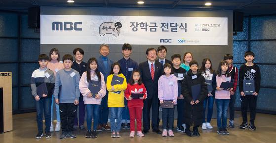 서상목 회장, 변창립 부사장을 비롯해 한국사회복지협의회와 MBC 주요 관계자들이 무한도전 장학생들과 함께 전달식 후 기념촬영을 하고 있다.