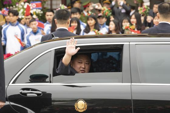 김정은 북한 국무위원장이 26일 특별열차 편으로 베트남 랑선성 동당역에 도착한 뒤 전용차량에 탑승해 하노이로 떠나면서 환영나온 주민들에 손을 흔들고 있다.[연합뉴스]