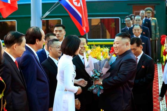 26일 김정은 북한 국무위원장이 중국과 접경지역인 베트남 랑선성 동당역에 도착해 환영단으로부터 꽃다발을 받고 있다. [연합뉴스]