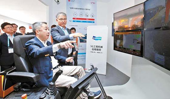 두산그룹 박정원 회장이 지난달 상하이에서 열린 '바우마 차이나' 에서 5G 원격제 어기술을 활용해 인천공장에 있는 굴삭기를 작동하고 있다. [사진 두산그룹]