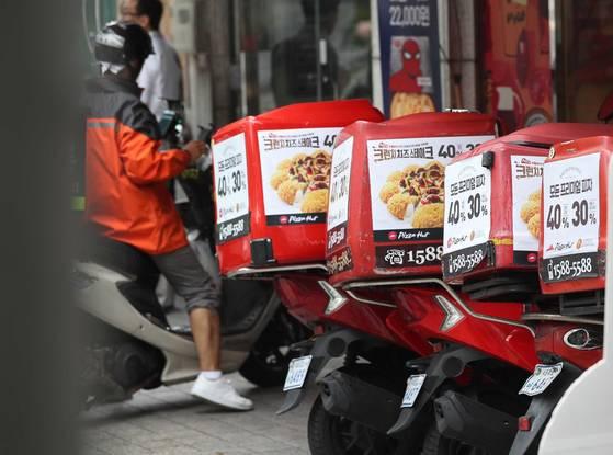 치솟는 배달용 오토바이 보험료로 인해 자영업자의 부담이 가중되고 있다. 서울 마포 한 피자집 앞에 배달 오토바가 세워져 있다. [중앙포토]