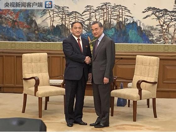 28일 베이징에서 이길성 북한 외무성 부상(왼쪽)이 왕이 중국 국무위원 겸 외교부장(오른쪽)과 만나 악수하고 있다. [사진=중국 외교부]