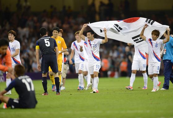 2012년 8월 10일, 영국 카디프 밀레니엄 스타디움에서 2012 런던올림픽 축구 동메달 결정전에서 동메달을 획득한 선수들이 태극기를 들고 기뻐하고 있다. [ 올림픽사진공동취재단 ]
