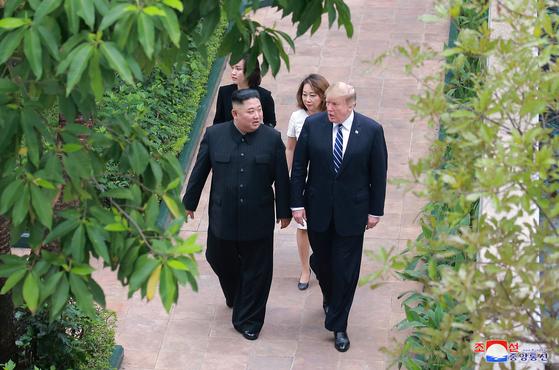 지난달 28일 도널드 트럼프 미국 대통령(오른쪽)과 김정은 북한 국무위원장(왼쪽)이 북ㆍ미 정상회담 장소인 베트남 하노이의 메트로폴 호텔 정원을 산책하고 있다. 북한의 조선중앙통신을 비롯한 북한 매체는 북ㆍ미 정상회담 소식을 전하면서 합의문 없이 끝난 점에 대해선 언급이 없었다. [사진 조선중앙통신=AP]