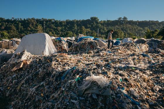 필리핀에 불법 수출됐던 한국산 쓰레기가 잔뜩 쌓여 있다. 그린피스 필리핀 사무소 관계자가 현장조사를 벌이는 모습. [연합뉴스]