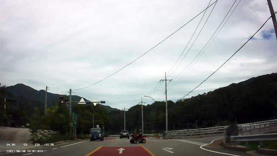 사륜오토바이가 도로를 횡단하는 모습. [사진 경남경찰청]