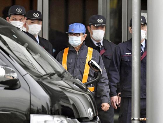 카를로스 곤 전 닛산자동차 회장으로 추정되는 인물이 6일 모자와 마스크로 얼굴을 가린 채 도쿄구치소를 나서고 있다. 곤 전 회장은 이날 보석 10억엔을 내고 풀려났다. [AP=연합뉴스]