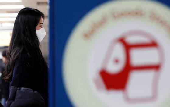 5일 서울 성북구 안암역 승강장에 설치된 구호용품 보관함의 방독면 그림 뒤로 마스크를 착용한 시민이 보인다. [뉴시스]