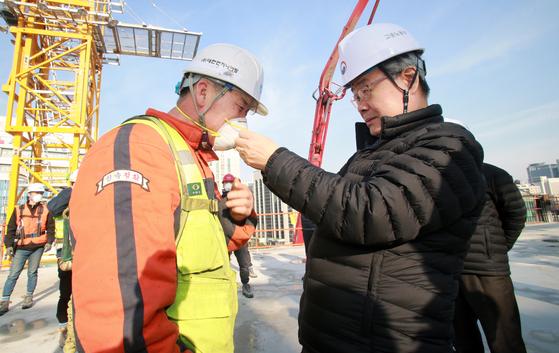 이재갑 고용노동부 장관이 22일 오후 건설현장에서 근로자에게 마스크를 나눠주고 있다. [고용노동부]