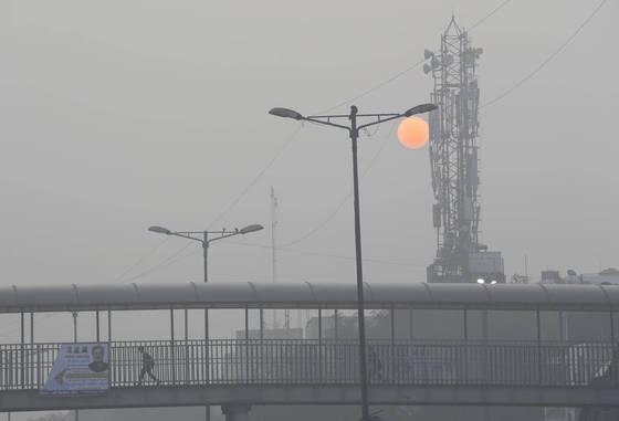 인도 뉴델리의 11월은 한 낮의 해도 뿌연 매연 속에 희미한다. 2017년 11월 한 학생이 육교를 건너가고 있다.[AP=연합뉴스]