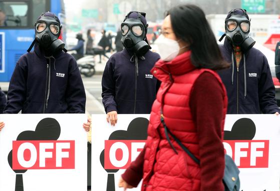 6일 오전 서울 광화문 광장에서 석탄발전 OFF 미세먼지 BYE 피켓 퍼포먼스를 펼치는 녹색연합 활동가들 앞으로 마스크를 쓴 한 시민이 지나고 있다.[뉴스 1]