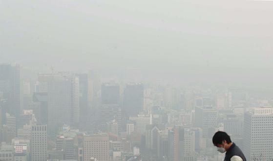 서울이 미세먼지에 6일째 갇혔다. 6일 한 시민이 미세먼지에 덮인 서울 시내를 바라보고 있다. [중앙포토]