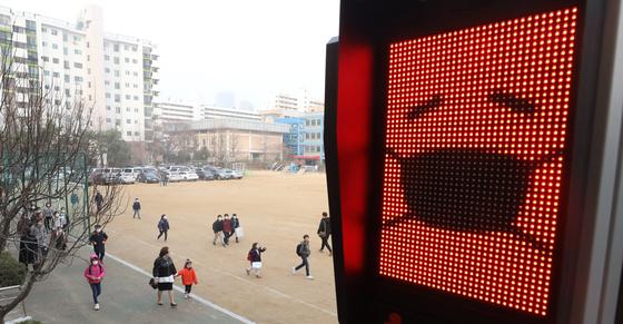 수도권 미세먼지 비상저감조치가 6일째 시행되고 있는 6일 오전 서울 영등포구 여의도초등학교에 설치된 미세먼지 신호등에 빨간불이 들어와 있다 [뉴스1]