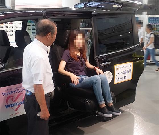 일본 도쿄 토요타자동차 복지차량(웰캡) 전시장 매니저(왼쪽)가 손님에게 휠체어 자동장치를 설명하고 있다. 일반 판매한다. [신성식 기자]
