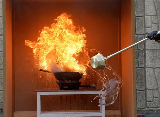 6일 대전 119시민체험센터에서 식용유 화재 시연이 실시했다. 소방관이 불이 붙은 식용유에 물을 붓자 오히려 화염이 치솟고 있다. 프리랜서 김성태