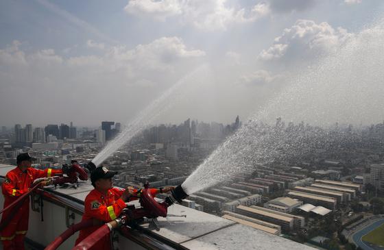 지난달 1일 방콕의 초미세먼지 수치가 치솟자 빌딩 옥상에서 소방용 호수로 상공에 살수하는 모습. [EPA=연합뉴스]