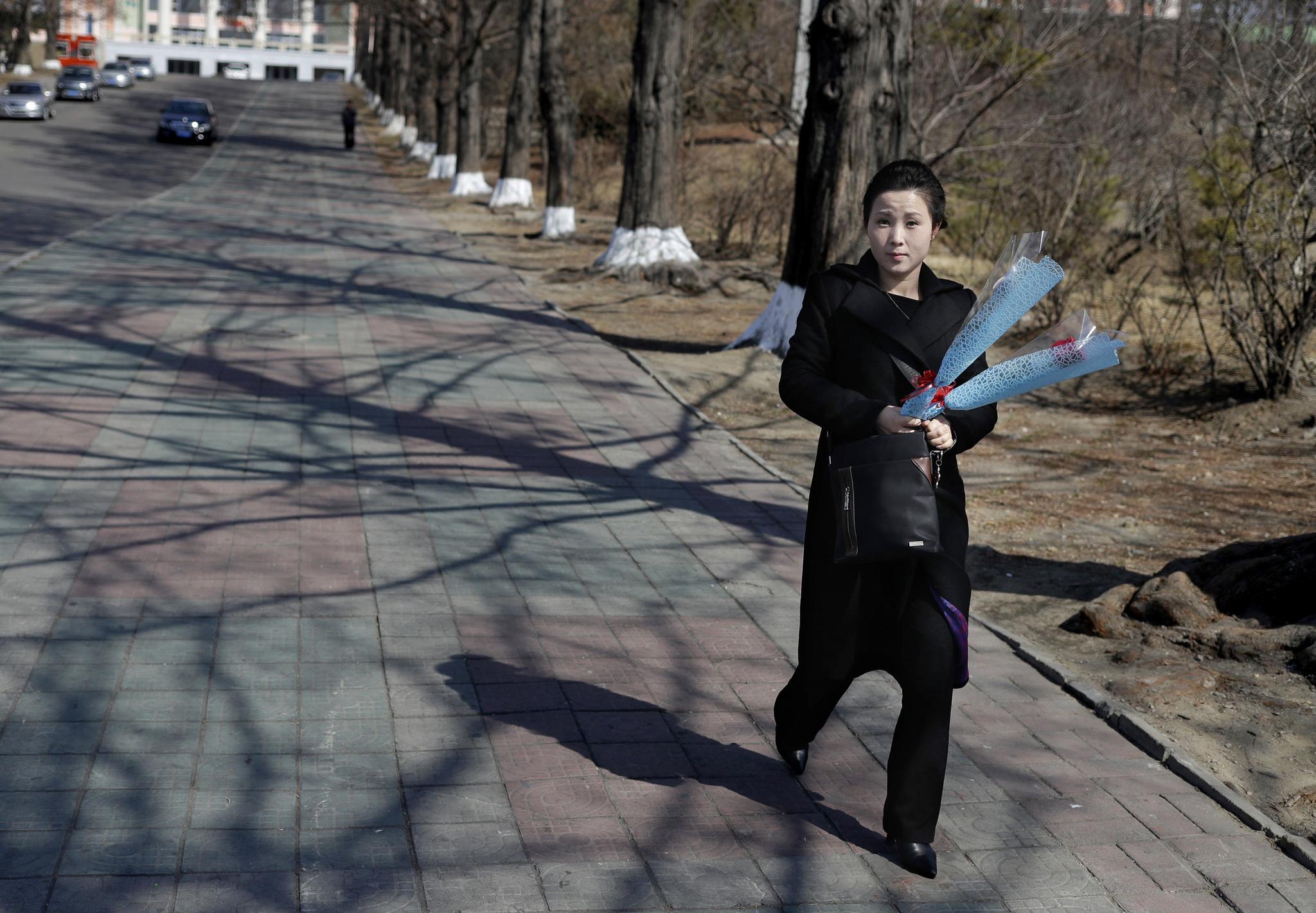 국제부녀절로 휴일인 8일 한 평양여성이 꽃을 들고 거리를 걷고 있다. [AP=연합뉴스]