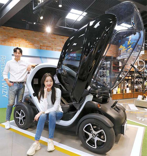 7일 서울 영등포구 타임스퀘어 일렉트로마트에서 모델들이 전기차 '트위지'를 선보이고 있다. 이마트는 전국 25개 매장에서 초소형 전기차인 르노삼성의 '트위지' 판매에 나선다고 밝혔다. [뉴시스]
